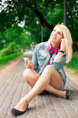 Young blond girl listening music — Stock Photo
