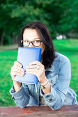 Beautiful young woman with book in park — Stock Photo