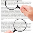 Hands holding magnifying glass reading document — Stock Photo #30345835
