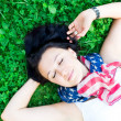 Beautiful girl lying on a grass — Stock Photo