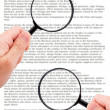 Hands holding magnifying glass reading document — Stock Photo #30648519