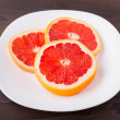 Slice of grapefruit on a palte — Stock fotografie