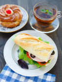 Breakfast with sandwich, tea and cake — Stock Photo