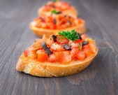 Tomato bruschetta topped with olive — Stock Photo