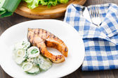 Grilled salmon with cucumber salad — Stock Photo
