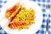 Honey chicken skewers with grilled corn salad — Photo