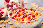Sugar coated corn flakes with milk and pomegranate — Stock Photo