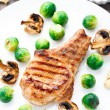 Grilled pork chop with brussels sprouts — Stock Photo