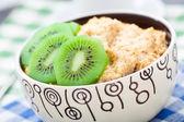 Bowl of oats porridge with kiwi — Stock Photo