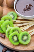 Fruits with chocolate on a stick — Stock Photo
