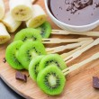Fruits with chocolate on a stick — Stock Photo #47255707