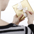 Young woman holding a present — ストック写真