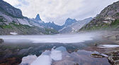 Mountain landscape. Mist over lake with ice — Stok fotoğraf
