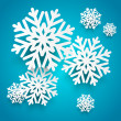 Paper snowflakes on blue background — Stock Vector