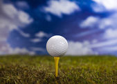 Golf ball on green grass over a blue sky — Stock Photo
