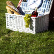 Picnic basket with fruit bread and wine — Stock Photo