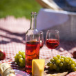 Wine and picnic basket on the grass - Stock Photo