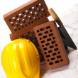 Brick, yellow hard hat, tools - Stock Photo