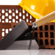 Hard hat with bricks and trowel - Stok fotoğraf