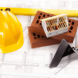 Hard hat with bricks and trowel - Stock Photo