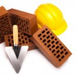 Brick, yellow hard hat, tools - Stockfoto