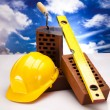 Brick, yellow hard hat, tools - Foto Stock