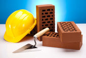 Hard hat with bricks and trowel — Stock Photo