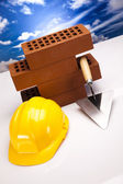Hard hat with bricks and trowel — Stock fotografie