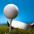 Golf ball on green grass over a blue background — Stock Photo #18849919