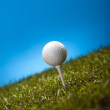 Golf ball on green grass over a blue background — Stock Photo #18852535
