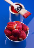 Can of red paint, brush and bowl of strawberry — Stock Photo