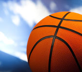 Basketball ball over blue sky background — Stock Photo