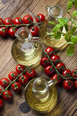 Olive oil with bunches of cherry tomatoes — Stock Photo