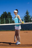 Woman standing near tennis grid — ストック写真