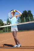 Woman standing near tennis grid — Photo