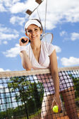 Woman standing near tennis grid — Stock fotografie
