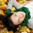 Woman lying on the leaves in the park — Stock Photo