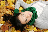 Woman lying on the leaves in the park — Stok fotoğraf