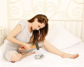 Angry woman smashing alarm clock — Stock Photo