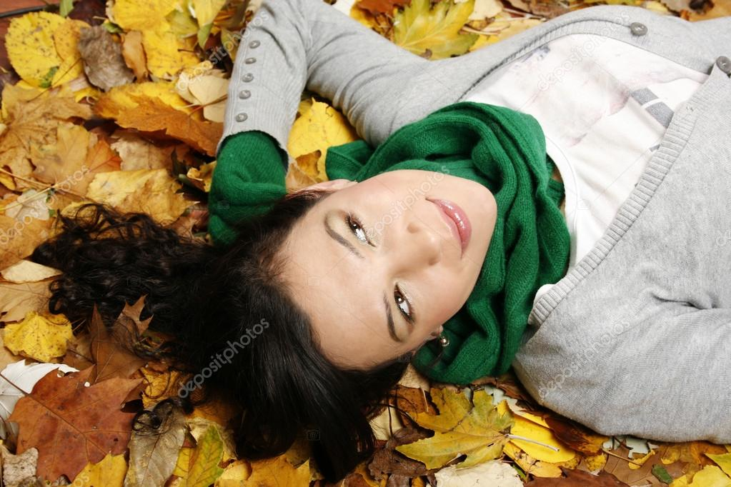 Young woman lying on the leaves in the park  — Stock Photo #13591160
