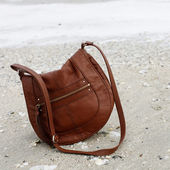 Brown purse on sand — Stock Photo