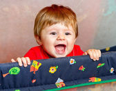 Baby girl standing in cot — Stock Photo