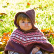 Baby with autumn leaf — Stockfoto
