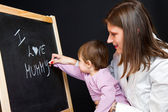 Mother and little daughter writing on a blackboard — Stock Photo