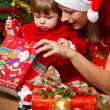 Young mother with baby at Christmas tree — Stock Photo #15727589