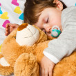 Sweet child sleeping with teddy bear - Foto Stock
