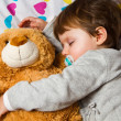 Sweet child sleeping with teddy bear — Stock Photo