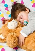 Sweet child sleeping with teddy bear — Stock Photo