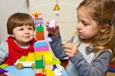 Little girls playing with building bricks — Stock Photo