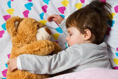 Sweet child sleeping with teddy bear — Stockfoto